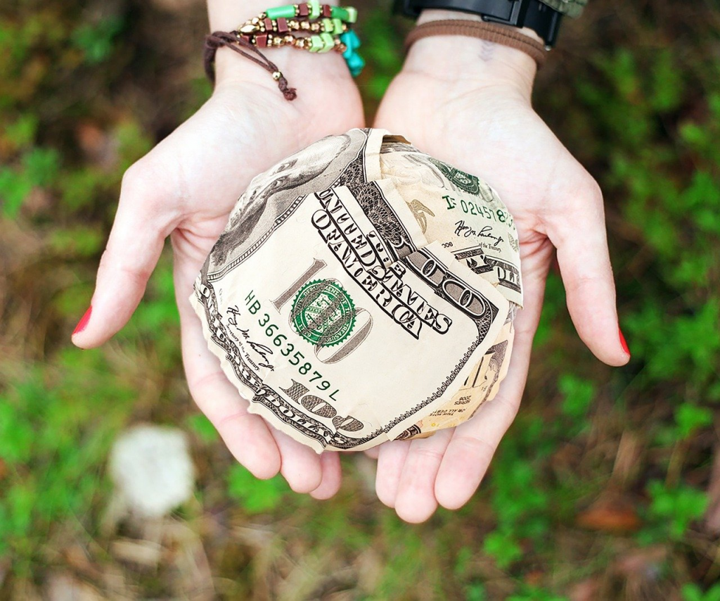 Hands holding dollars to demonstrate converting volunteers to donors