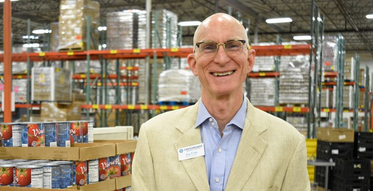 Jay Cole, Executive Director of CCS, standing in front of food pantry